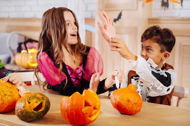 Tricks mit schwester. netter dunkeläugiger junge, der skelett-halloween-kostümüberzugstricks mit älterer schwester trägt