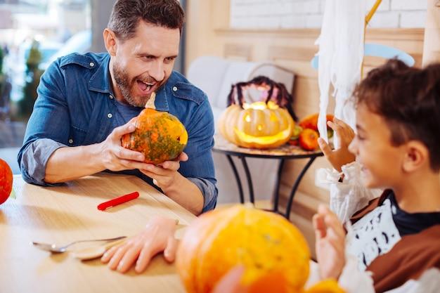 Tricks mit sohn. lustiger liebender vater, der sich einfach erstaunlich fühlt, während er streiche mit seinem niedlichen sohn spielt, der skelettkostüm trägt