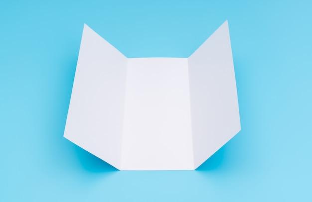 Trifold weiße vorlage papier auf blauem hintergrund.