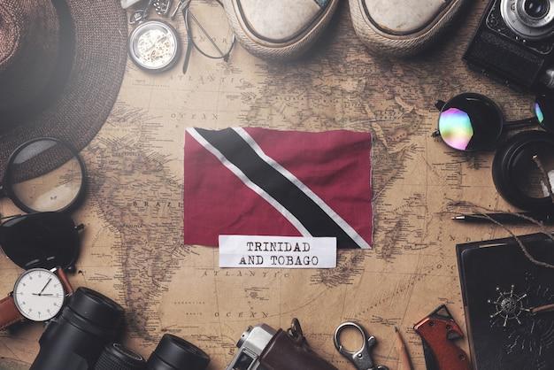 Trinidad und tobago-flagge zwischen dem zubehör des reisenden auf alter weinlese-karte. obenliegender schuss
