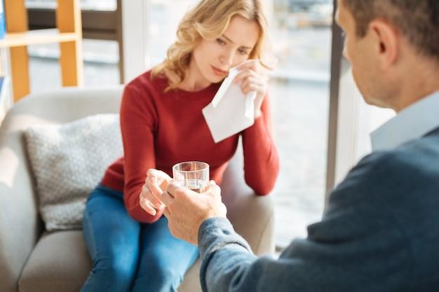 Trink es. selektiver fokus eines glases wasser, das einer traurigen unglücklichen patientin beim weinen gegeben wird