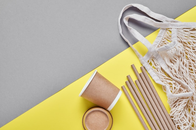 Trinkbraune röhrenstrohhalme aus papier und maisstärke, netzmarkttasche und leere kaffeetassen aus papier auf einem trendigen grauen und gelben hintergrund. null abfall und plastikfreies konzept. draufsicht.