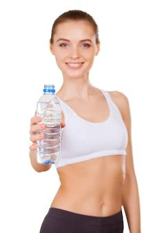 Trinke genug. schöne junge frau in sportkleidung, die eine flasche mit wasser hält und lächelt, während sie isoliert auf weiß steht
