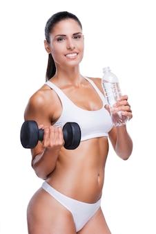 Trinke genug! schöne junge frau in weißem bh und höschen, die flasche mit wasser und hantel hält, während sie isoliert auf weiß steht