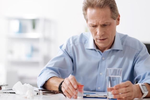 Trinken oder nicht. sehr ernste männliche person, die blaues hemd trägt, das glas wasser hält, während seine stirn runzelt