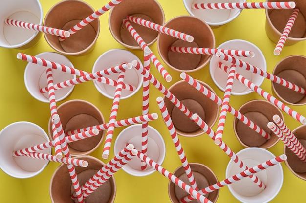 Trinken roter röhrenstrohhalme aus papier und maisstärke in leeren pappkaffeetassen auf einem trendigen gelben hintergrund. null abfall und plastikfreies konzept. draufsicht.