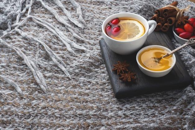 Trinken sie aus wilden rosenbeeren mit zitrone und honig zimt. vitamin nützliche abkochung von hagebutten. gemütliches zuhause konzept der wintergetränk textfreiraum