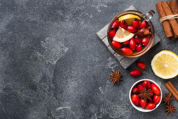 Trinken sie aus wilden rosenbeeren mit zitrone und honig zimt. vitamin nützliche abkochung von hagebutten. hintergrund