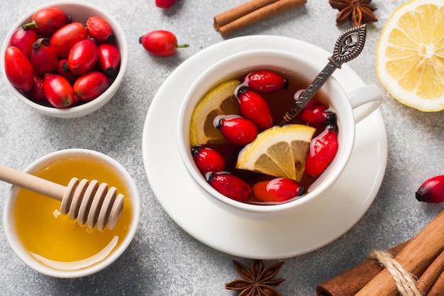 Trinken sie aus wilden rosenbeeren mit zitrone und honig zimt. vitamin nützliche abkochung von hagebutten.