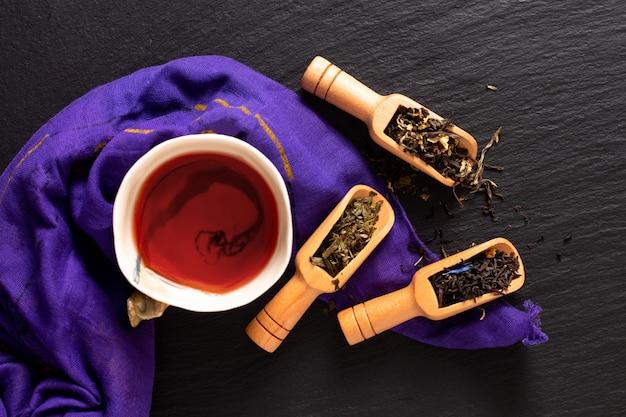 Trinken sie draufsicht des konzeptes des organischen kräutertees mit teeschale auf schwarzem schiefersteinbrett mit kopienraum