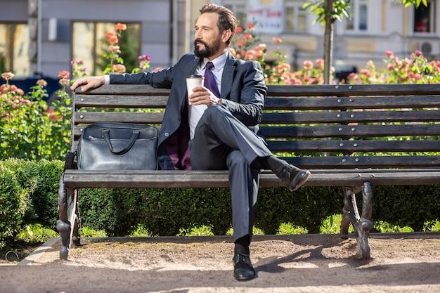 Trinken sie einen schluck. angenehmer selbstbewusster geschäftsmann, der auf der bank sitzt, während kaffee trinkt