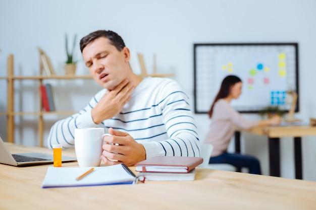 Trinken sie heißen tee. kranker mann, der den mund offen hält und die augen schließt, während er heißen tee trinkt