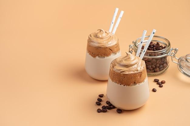 Trinken sie mit geschlagenem kaffeeschaum und milch an einer orangefarbenen wand. dalgona-kaffee. seitenansicht, kopienraum.