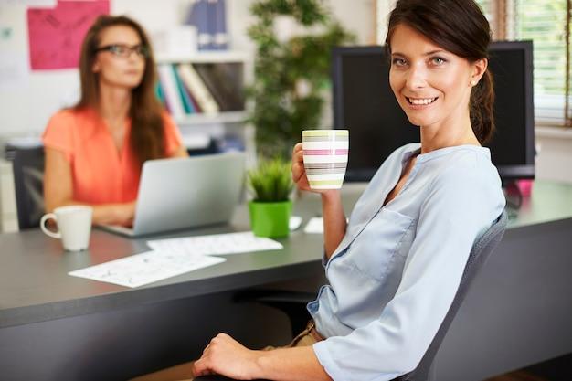 Trinken sie während der arbeit einen schluck heißen kaffee