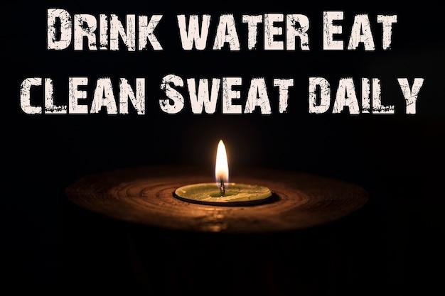 Trinken sie wasser essen sie sauberen schweiß täglich - weiße kerze mit dunklem hintergrund - in einem hölzernen kerzenständer.
