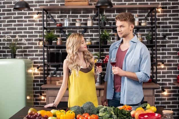 Trinken und kochen. glückliches liebespaar, das zusammen wein trinkt und gesundes abendessen in der küche kocht