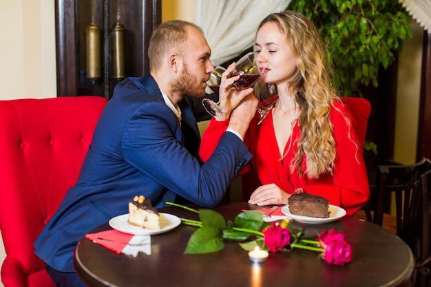 Trinkende bruderschaft der jungen paare bei tisch im restaurant