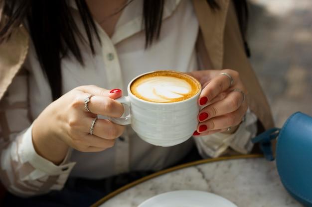 Trinkende cappuccinotasse der frau