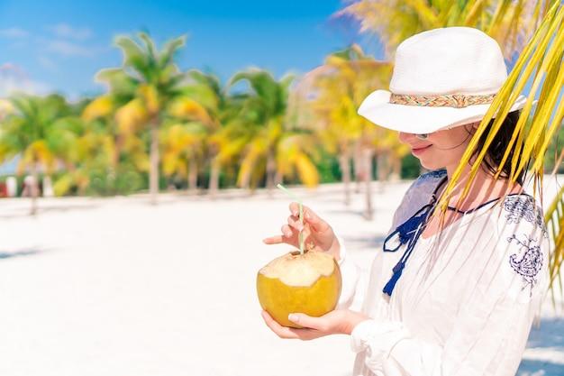 Trinkende kokosmilch der jungen frau am heißen tag auf dem strand.