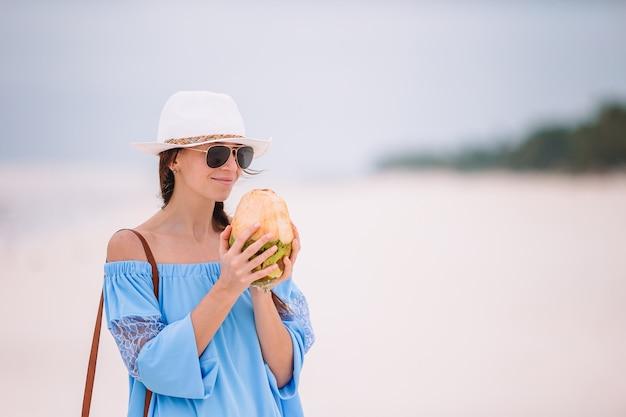 Trinkende kokosmilch der jungen frau während der tropischen ferien