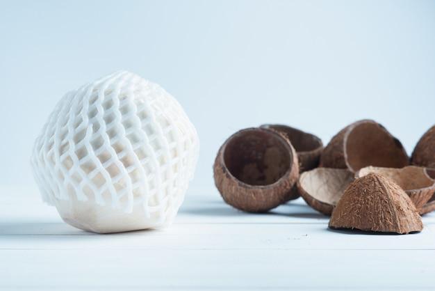 Trinkende kokosnuss und aufgeteilte braune kokosnüsse im weißen hintergrund