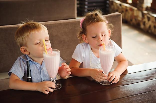 Trinkende milchshakes des kleinen jungen und des mädchens in einem café draußen.