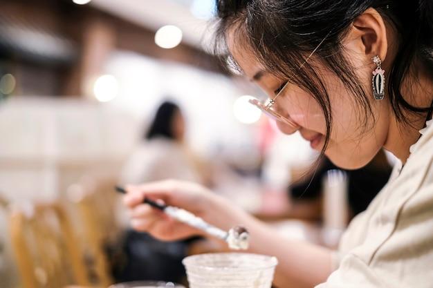 Trinkende schokolade frappe der asiatischen netten frau im caféladen