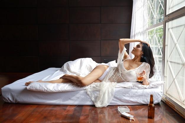Trinkender alkohol der betrunkenen asiatischen frau und rauchende zigarette beim lügen im bett