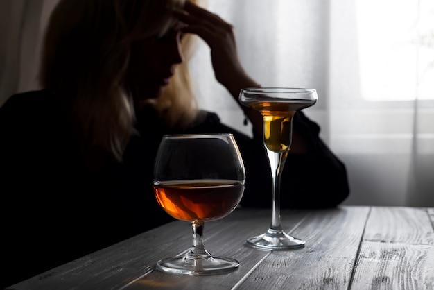 Trinkender alkohol der frau allein, der ihr fenster heraus schaut.