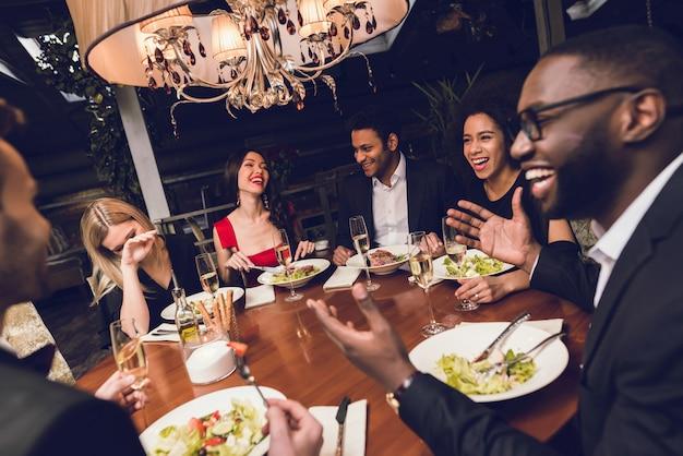 Trinkender alkohol der jungen leute in einem restaurant.