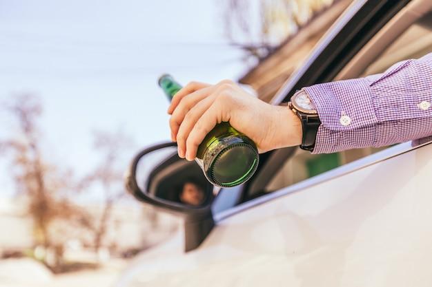Trinkender alkohol des mannes beim fahren des autos