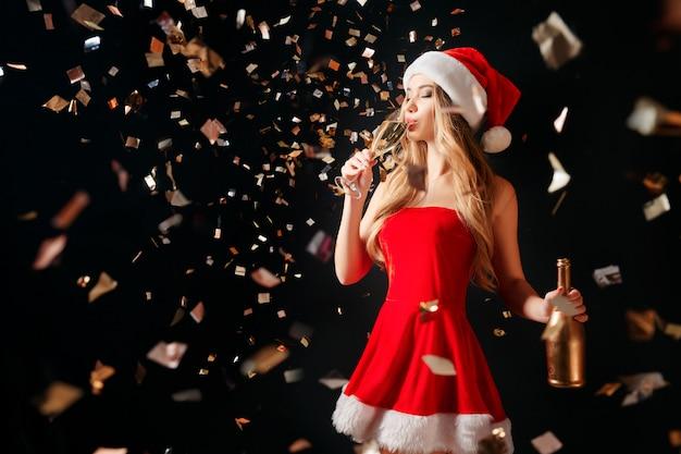 Trinkender champagner der frau im konfetti