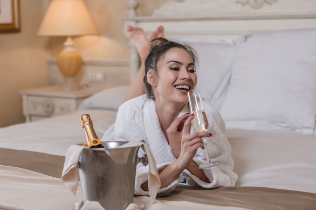 Trinkender champagner der lachenden frau auf bett