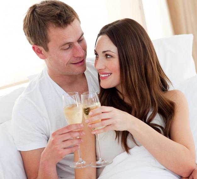 Trinkender champagner der romantischen paare, der im bett liegt