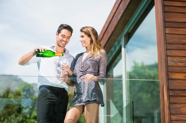 Trinkender champagner des glücklichen paars am balkon im erholungsort