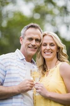 Trinkender champagner des glücklichen paars draußen