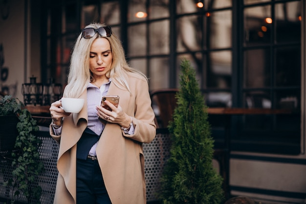 Trinkender kaffee der älteren geschäftsfrau außerhalb des cafés und unterhaltung am telefon