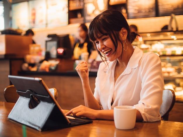 Trinkender kaffee der asiatin im café und anwendung der laptop-computers für arbeitsgeschäft