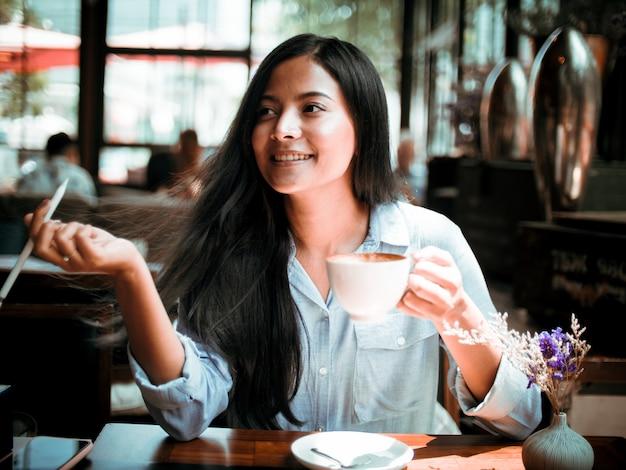 Trinkender kaffee der asiatin und arbeiten mit laptop-computer im café