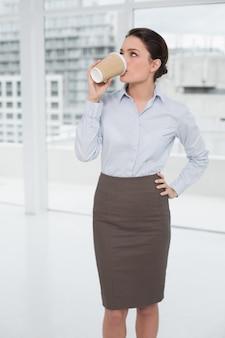 Trinkender kaffee der eleganten geschäftsfrau im büro