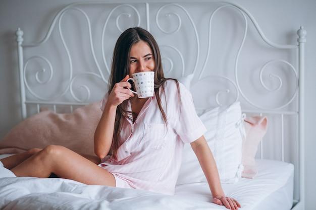 Trinkender kaffee der frau im bett