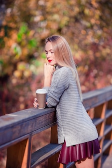 Trinkender kaffee der frau im herbstpark