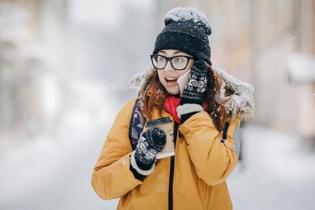 Trinkender kaffee der frau und unterhaltung auf dem phobne draußen im winter