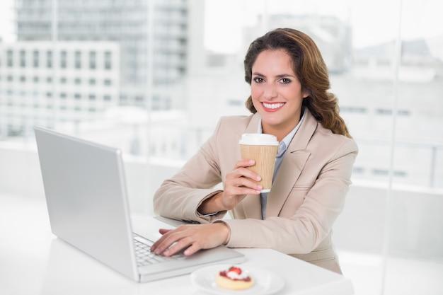 Trinkender kaffee der geschäftsfrau an ihrem schreibtisch unter verwendung des laptops, der an der kamera lächelt