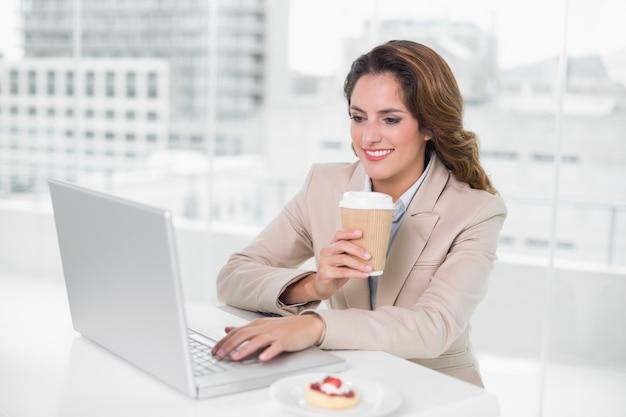 Trinkender kaffee der geschäftsfrau an ihrem schreibtisch unter verwendung des laptops