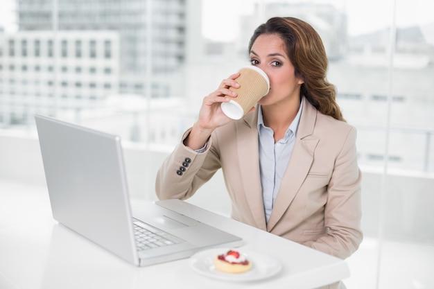 Trinkender kaffee der geschäftsfrau an ihrem schreibtisch vor laptop