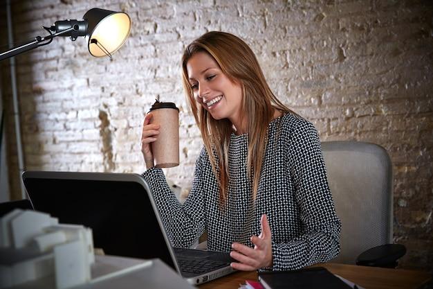 Trinkender kaffee der geschäftsfrau, der im büro arbeitet