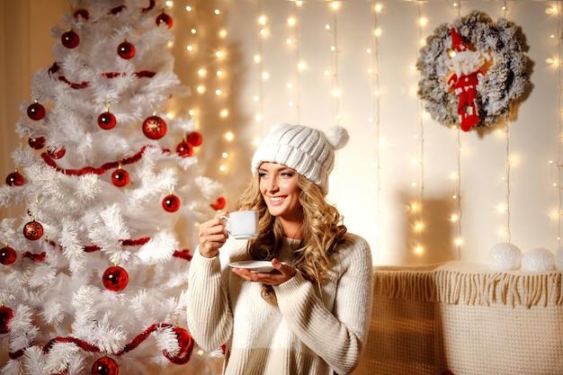 Trinkender kaffee der glücklichen blondine, innenraum mit weihnachtsdekoration