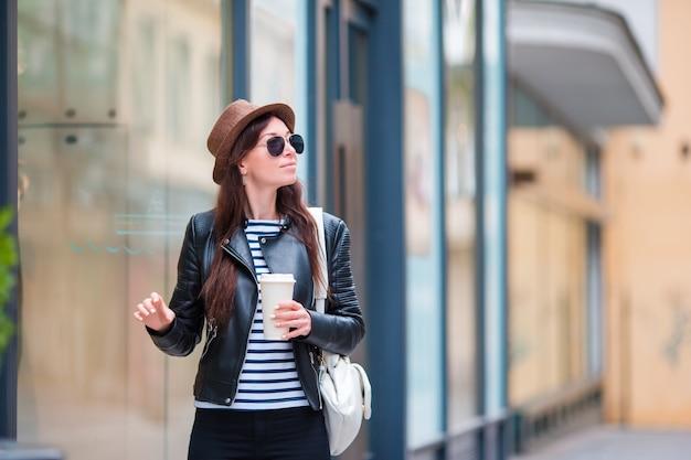 Trinkender kaffee der glücklichen jungen städtischen frau in der europäischen stadt. touristische frau der reise mit heißem getränk draußen während der feiertage in europa.