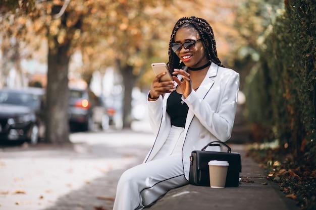 Trinkender kaffee der jungen afrikanischen frau und anwendung des telefons